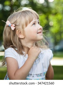 Portrait of charming little girl in a summer park
