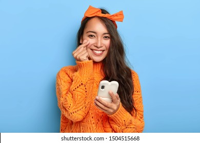 Portrait of charming lovely lady in stylish orange clothes, makes korean heart sign, expresses her love and sympathy, uses mobile phone for shopping online, sends notification. Body language concept