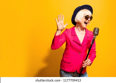 Portrait of charming modern grandmother holds up the microphone stand and sings a raised palm top isolated on vivid yellow background with copy space for text