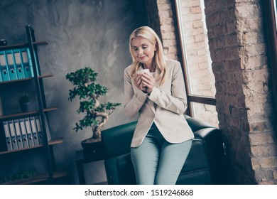 Portrait of charming peaceful dreamy middle aged woman hold cup mug with coffee smell enjoy rest before hard start-up workshop seminar wear beige blazer sit  on couch in enterprise office