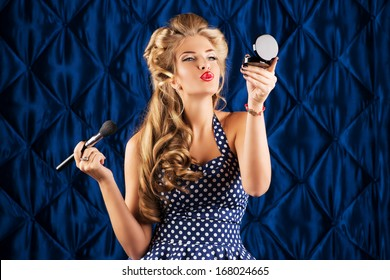 Portrait of a charming pin-up girl doing makeup in front of a mirror.
