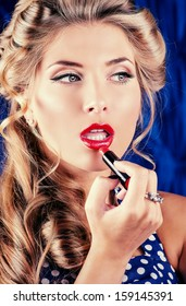 Portrait of a charming pin-up girl painting lips with red lipstick.