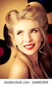 Portrait of a charming pin-up woman with retro hairstyle and make-up posing with vinyl record.