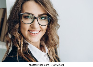 Portrait of a charming positive business woman in a suit and in glasses