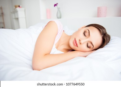 Portrait of charming, pretty, cute, nice, brunette girl lying in bed under blanket, sleeping with close eyes, putting, holding hands under cheek, having sweet dreams and good sleep