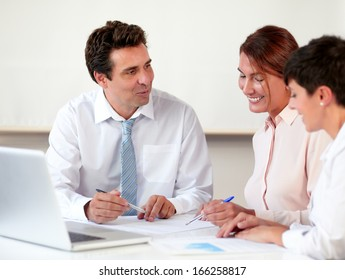 Portrait of charming professional group working on documents while smiling and sitting on office desk