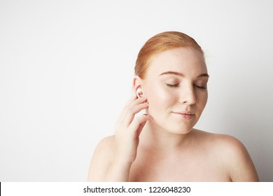 Portrait of charming redhead woman with romantic smile and closed eyes listening music with wireless earphone in ear over background