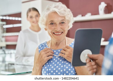 Portrait of charming senior lady with grey curly hair wearing blue elegant polka dot dress, smiling and looking at camera while holding hands on amazing pearl necklace with blur background behind.