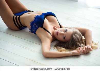 Portrait of a charming sexy woman in in fashionable luxury designer underwear lingerie lying on the bed and looking at camera