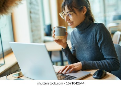 Portrait of charming smiling business woman in glasses working on laptop computer. Female copywriter sitting at desk and typing on keyboard, working on project, writing down ideas into netbook