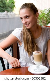 portrait of charming smiling woman with coffee in outdoor city cafe