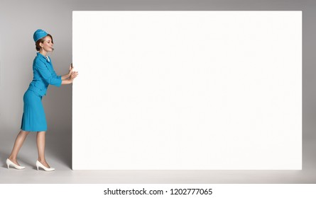 Portrait of charming stewardess wearing in blue uniform. Empty blank copyspace.