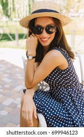 Portrait of charming style woman in the summer park wearing summer hat and black sunglasses and cute dress. She is looking at camera with wonderful smile. Background summer park. Summer holiday.