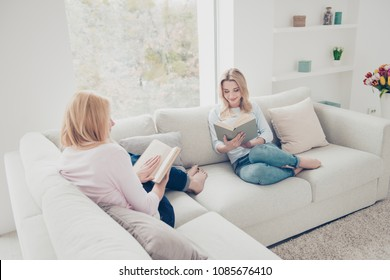 Portrait of charming stylish smart mother and daughter sitting with legs on couch holding books in hands detective lover enjoying freetime in comfortable cozy atmosphere modern white apartments
