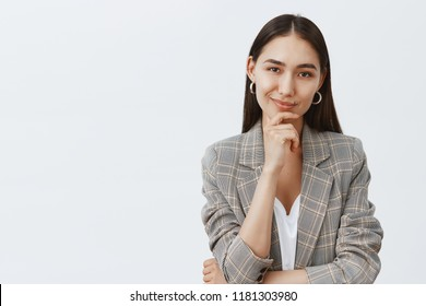 Portrait of charming successful female in stylish jacket over t-shirt, holding hand on chin and smirking while having great idea in mind, thinking about something curious over gray background