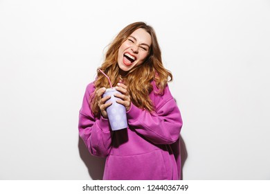 Portrait of charming woman 20s wearing sweatshirt drinking soda from paper cup using straw isolated over white background