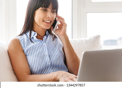 Portrait of charming woman 40s in elegant clothes using cell phone and laptop while sitting on couch in bright apartment