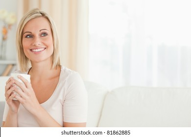 Portrait of a charming woman holding a cup of tea looking away from the camera