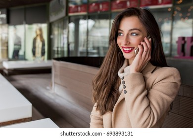 Portrait of charming woman with long dark hair is sitting on the street. She has red lips and wonderful smile. She is talking on the phone with great emotions. Good day. Street look.