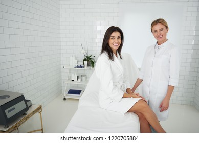Portrait of charming woman in soft bathrobe sitting on daybed while beautician in white lab coat standing beside her. Ladies looking at camera and smiling