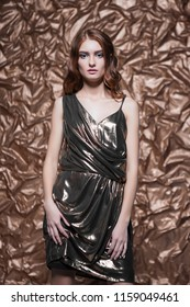 Portrait of charming woman wearing glossy dress posing in the studio