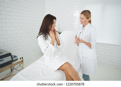 Portrait of charming woman in white bathrobe sitting on daybed and checking results of skin care treatment while cosmetologist holding looking-glass