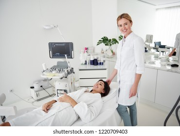 Portrait of charming woman in white bathrobe lying on daybed while beautician looking at camera and smiling
