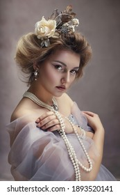 Portrait of charming young aristocratic lady with pearl jewelry wearing romantic dress