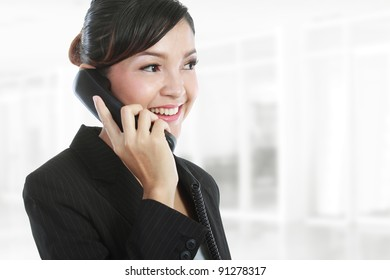 Portrait of charming young business woman on phone call at office