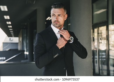 Portrait of a charming young businessman dressed in suit standing outside a glass building and touching his tie