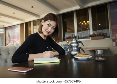 Portrait of charming young Korean entrepreneur looking at camera while planning working process and thinking about successful ideas for personal business project sitting indoors