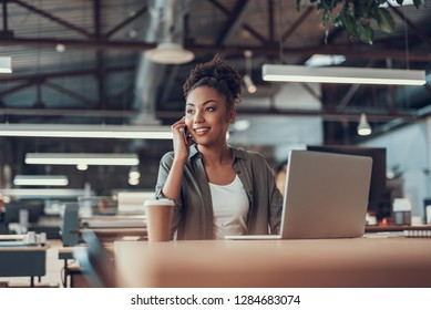 Portrait of charming young lady having phone conversation while sitting at office table with notebook and cup of coffee. She is looking away and smiling