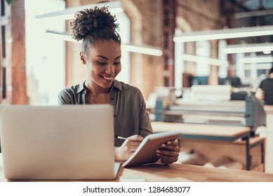 Portrait of charming young lady writing on notebook with pencil. She is sitting at table with laptop and smiling