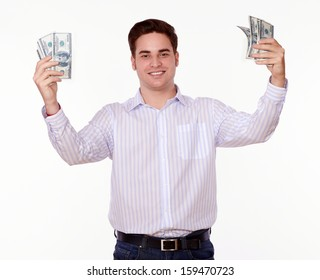 Portrait of a charming young man standing while holding cash money and smiling at you on isolated studio
