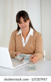 Portrait of a charming young woman counting cash money for buying
