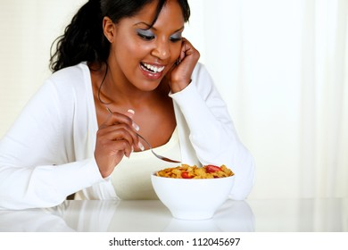 Portrait of a charming young woman eating a bowl of cereals with strawberries at soft colors composition. with copyspace