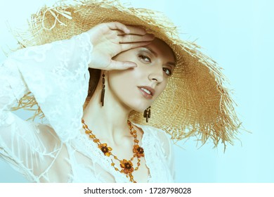 Portrait of a charming young woman in light elegant lace dress and a wide brim straw hat smiling happily at camera. Fashion shot, summer style. Happiness.