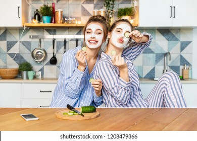 Portrait of charming young women fooling around at kitchen and having spa day with face masks. Two girls in comfy pyjamas. Youth and friendship concept. Blurred background