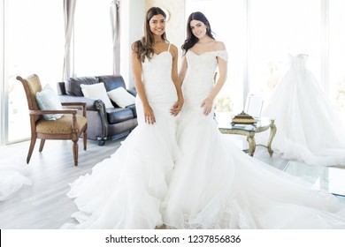 Portrait of charming young women wearing white gowns for their marriage in bridal salon
