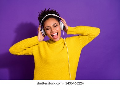 Portrait of charming youth touch headset listen sound track feel content wear yellow pullover isolated over purple background