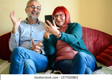 Portrait of Checking social media. Portrait of smiling blond woman using her mobile phone and text messaging while relaxing on sofa at home. beautiful couple of seniors or mature people at home hugged