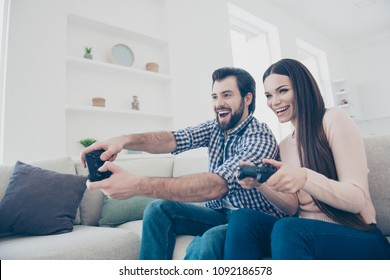 Portrait of cheerful active couple enjoying playing videogame on playstation in house holding console gamepad in hands, fans of xbox