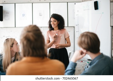 Portrait of cheerful African American lady with dark curly hair standing near board and happily speaking with colleagues in office. Young beautiful business woman giving presentation to coworkers