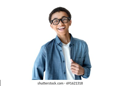 portrait of cheerful african american teenage boy in eyeglasses looking at camera isolated on white