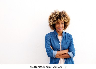 Portrait of cheerful african american woman with arms crossed on white background