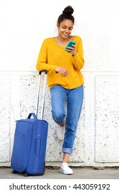 Portrait of cheerful african woman reading text message mobile phone and standing outside with suitcase