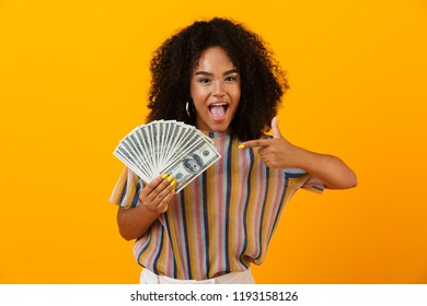 Portrait of a cheerful african woman standing isolated over yellow, showing money banknotes, pointing finger