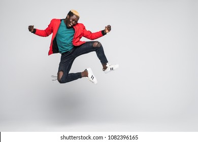 Portrait of a cheerful afro american man jumping isolated on a white background