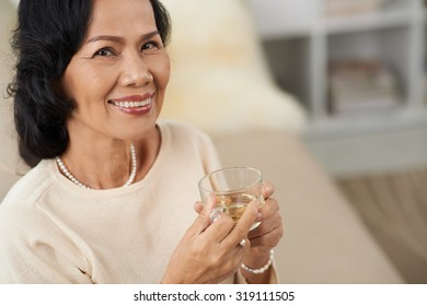 Portrait of cheerful aged woman with a cup of tasty floral tea