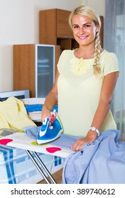 Portrait of cheerful american woman with iron and laundry